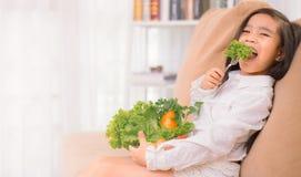亚裔逗人喜爱的女孩吃新鲜的沙拉,健康吃概念 库存照片