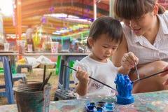 亚裔逗人喜爱的女孩婴孩和母亲绘五颜六色 免版税库存图片