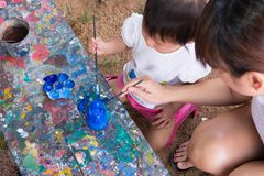 亚裔逗人喜爱的女孩婴孩和母亲绘五颜六色 免版税库存照片