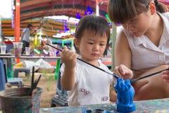 亚裔逗人喜爱的女孩婴孩和母亲绘五颜六色 免版税图库摄影