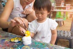 亚裔逗人喜爱的女孩婴孩和母亲绘五颜六色 库存照片
