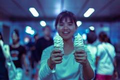 亚裔逗人喜爱的女性在城市拿着冰淇凌 免版税库存照片