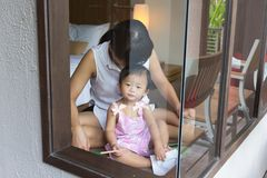 亚裔逗人喜爱的婴孩和母亲选址modren卧室 库存照片
