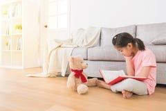 亚裔逗人喜爱的小女孩坐木地板 库存图片