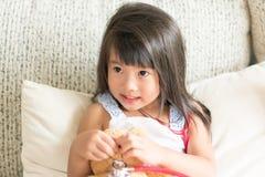 亚裔逗人喜爱的小女孩是微笑和扮演有stetho的医生 库存照片