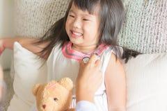 亚裔逗人喜爱的小女孩是微笑和扮演有stetho的医生 免版税库存照片