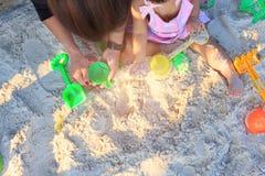 亚裔逗人喜爱的演奏沙子的女婴和父母靠岸 免版税图库摄影