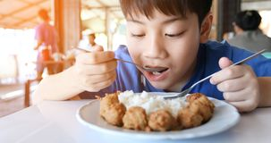 亚裔逗人喜爱的男孩吃早餐和看照相机与微笑面孔 库存照片