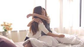 亚裔醒在早晨的妇女女同性恋的愉快的夫妇 亚洲女孩坐在家舒展在舒适卧室的床 股票录像