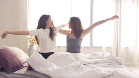 亚裔醒在早晨的妇女女同性恋的愉快的夫妇 亚洲女孩坐在家舒展在舒适卧室的床 影视素材