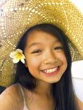 亚裔长的黑发女孩佩带草帽和白花 库存照片