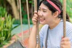 亚裔青少年的肥胖妇女笑滑稽愉快享用与摇摆 免版税库存图片
