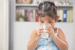 亚裔饮用的女孩少许牛奶 免版税库存图片