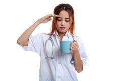 亚裔年轻女性医生得到了与一杯咖啡的头疼 免版税图库摄影