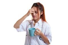 亚裔年轻女性医生得到了与一杯咖啡的头疼 库存照片