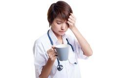 亚裔年轻女性医生得到了与一杯咖啡的头疼 免版税库存图片