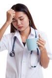 亚裔年轻女性医生得到了与一杯咖啡的头疼 库存图片