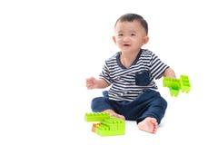 亚裔婴孩使用与在白色的塑料建筑玩具 免版税图库摄影