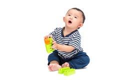 亚裔婴孩使用与在白色的塑料建筑玩具 免版税库存图片