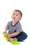亚裔婴孩使用与在白色的塑料建筑玩具 免版税库存照片