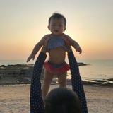 亚裔婴孩和母亲获得乐趣在日落时间 库存照片
