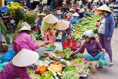 亚裔贸易商在街市上的卖新鲜蔬菜 免版税库存照片