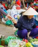 亚裔贸易商在街道开放的市场上的卖新鲜蔬菜 库存图片