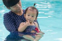 亚裔年轻母亲和逗人喜爱的一个演奏游泳池的年婴孩 免版税库存照片