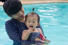 亚裔年轻母亲和逗人喜爱的一个演奏游泳池的年婴孩 库存照片