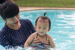 亚裔年轻母亲和逗人喜爱的一个演奏游泳池的年婴孩 图库摄影