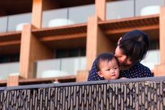 亚裔年轻母亲和逗人喜爱的九个月的婴孩享用游泳池 库存照片
