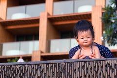 亚裔年轻母亲和逗人喜爱的九个月的婴孩享用游泳池 库存图片