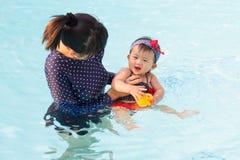亚裔年轻母亲和逗人喜爱的八个月的婴孩享用游泳池 图库摄影