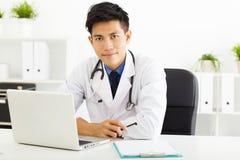 亚裔医生与膝上型计算机一起使用在办公室 库存图片