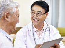 亚裔医生谈话与患者 免版税库存照片