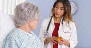 亚裔医生谈话与年长妇女在床上关于处方疗程 库存照片