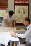 亚裔治疗师给脚 免版税库存图片