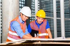 亚裔建筑师和监督员建筑工地的 免版税库存照片