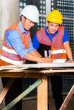 亚裔建筑师和监督员建筑工地的 免版税图库摄影