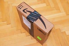 亚马逊最初在小包纸板箱的微笑箭头 免版税库存照片