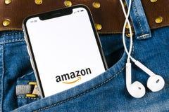 亚马逊购物在苹果计算机iPhone x屏幕特写镜头的应用象在牛仔裤装在口袋里 亚马逊购物的app象 亚马逊流动applic 免版税库存照片