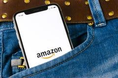 亚马逊购物在苹果计算机iPhone x屏幕特写镜头的应用象在牛仔裤装在口袋里 亚马逊购物的app象 亚马逊流动applic 库存图片