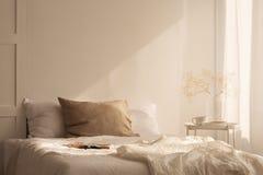 亚麻制板料离子加长型的床在有空的墙壁的最小的卧室 库存图片