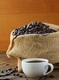 亚麻制袋子咖啡豆和一个杯子浓咖啡 库存图片
