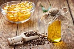 亚麻籽和油在瓶在木背景 库存图片
