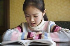 亚洲书女孩读取 免版税库存照片