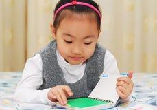 亚洲书逗人喜爱的女孩读取 免版税图库摄影