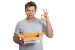 亚洲人举行一个开放箱子展示OK标志 免版税库存照片