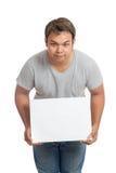 亚洲人举行一个空白的标志和低下他的头 库存照片