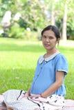 亚洲人孕妇是休闲在公园 免版税图库摄影
